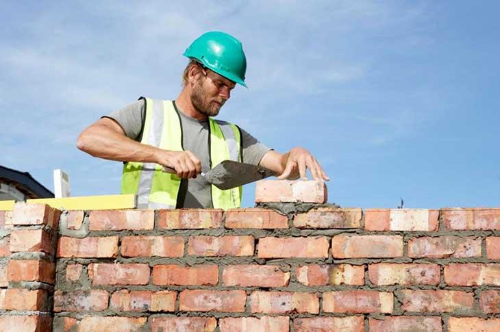 A bricklayer laying a brick wall.
