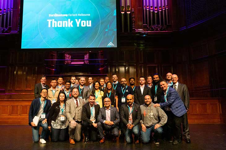 StartUpBootcamp's FinTech program participates posing for a photo in a large hall.