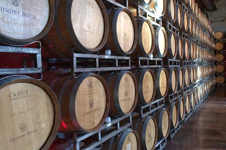 A line of wine barrels in a warehouse.