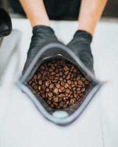 Coffee roaster holding a bag of roasted coffee beans.