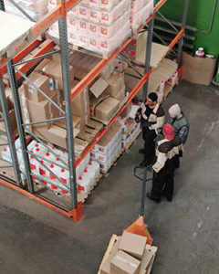 People working in a wholesale warehouse. Stocking products.
